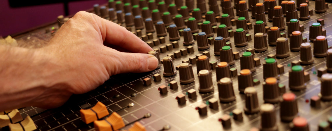 Making adjustments to mixing desk in mixing studio