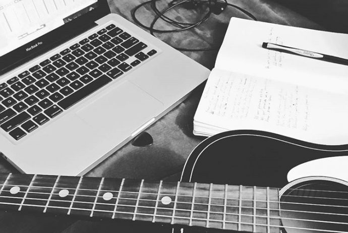 Guitar, computer and notebook for songwriting