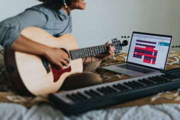 Songwriter playing guitar writing a song